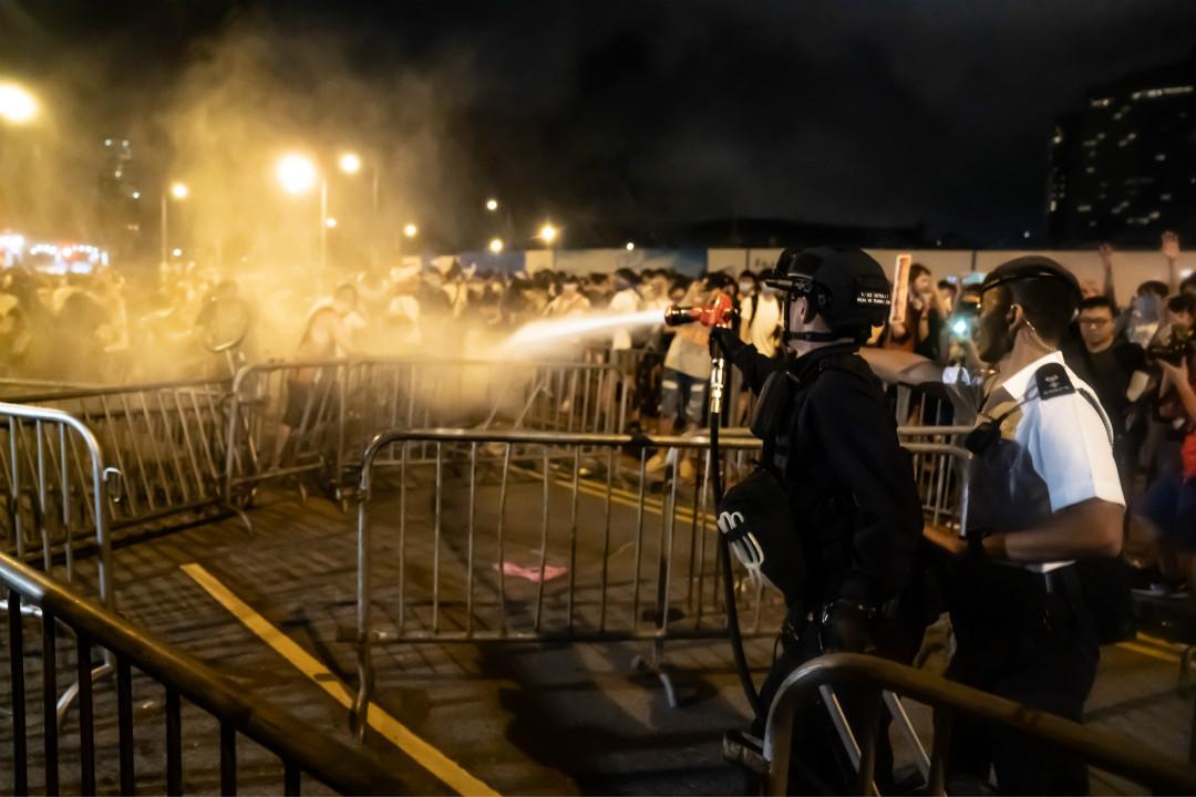 2019年6月10日凌晨,香港政府大樓前,警察向遊行結束後的留守者使用胡椒噴霧。 攝:Anthony Kwan/Getty Images