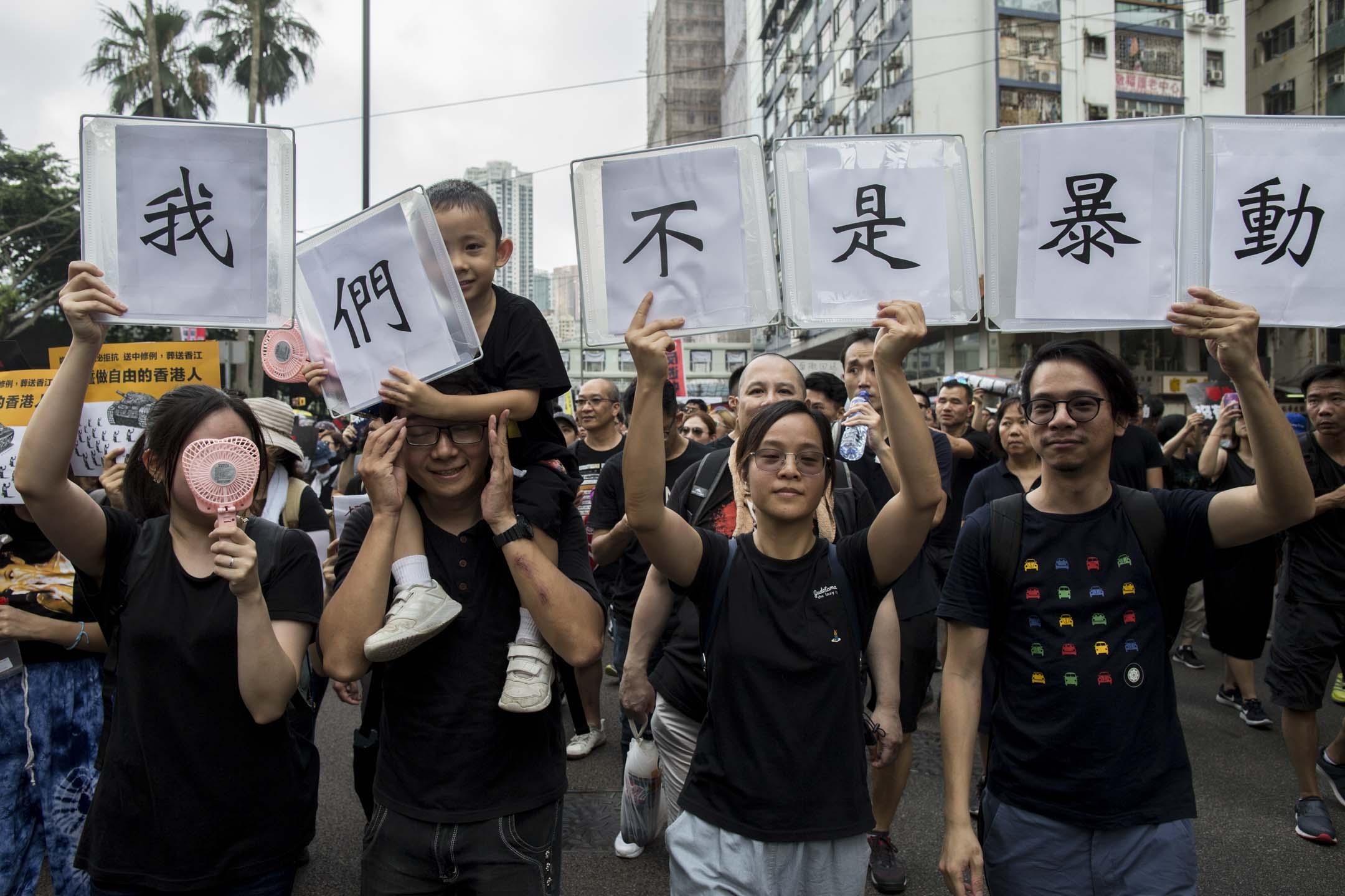 2019年6月16日,民陣反對《逃犯條例》修訂大遊行, 遊行人士高舉「我們不是暴民」標語參與其中。  攝:林振東/端傳媒