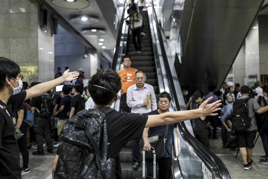 2019年6月24日,數百名示威者在灣仔稅務大樓採取不合作運動,嘗試癱瘓港府部份運作,迫使港府回應撤回《逃犯條例》修訂等訴求;期間有示威者協助引導受影響市民離開大樓,同時向市民解釋狀況,以至鞠躬致歉。 攝:Stanley Leung / 端傳媒