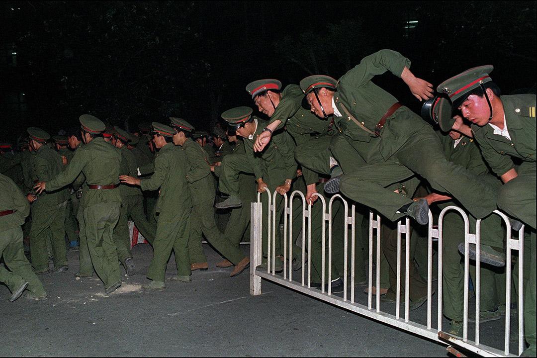 1989年6月4日,解放軍與示威者發生激烈衝突,士兵在天安門廣場上跨越障礙物。