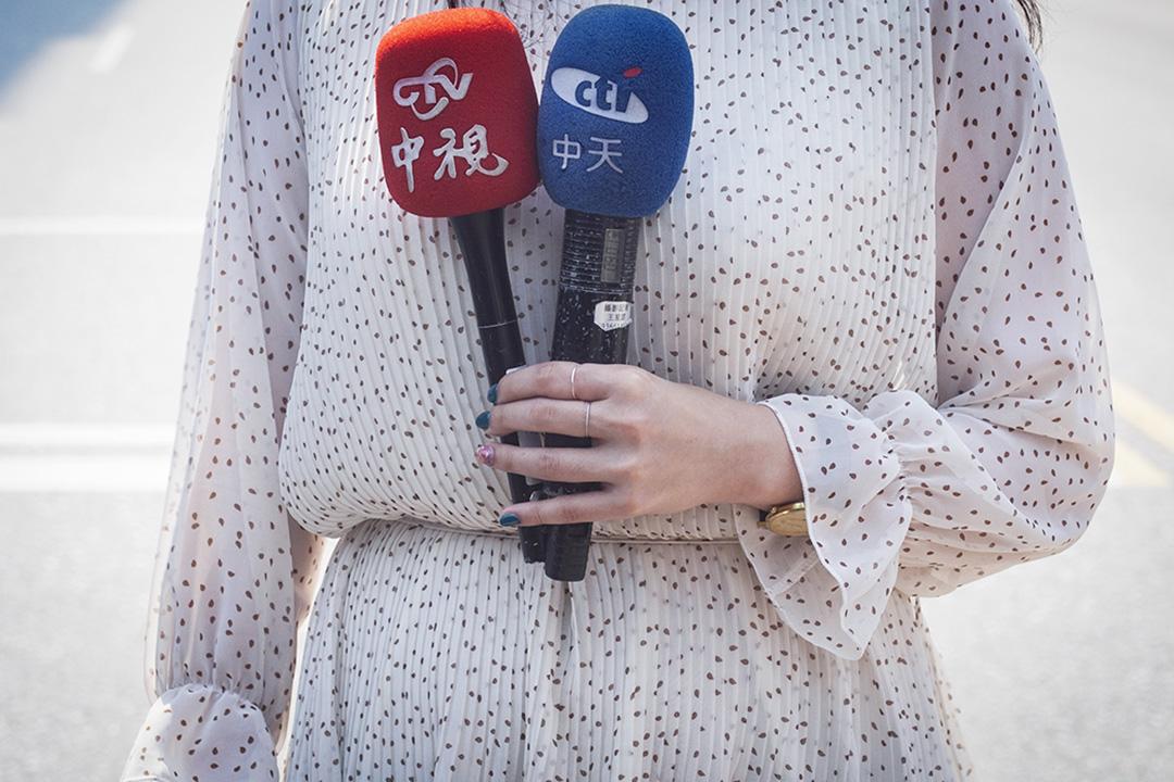 一名記者拿著中天電視的咪高峰。