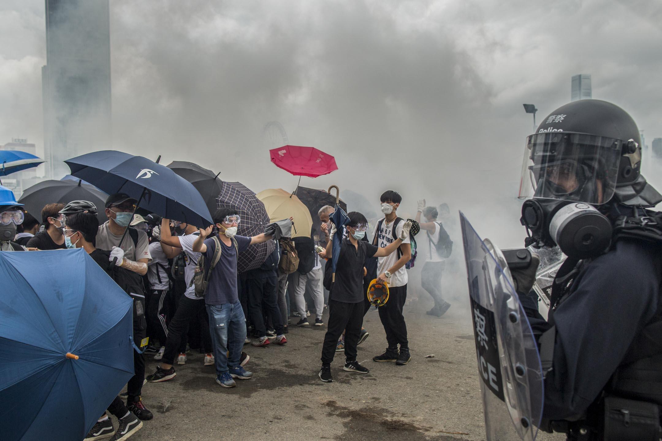 2019年6月12日,警方數十名速龍小隊在龍和道驅趕示威者,他們以雨傘來對抗。 攝:林振東/端傳媒
