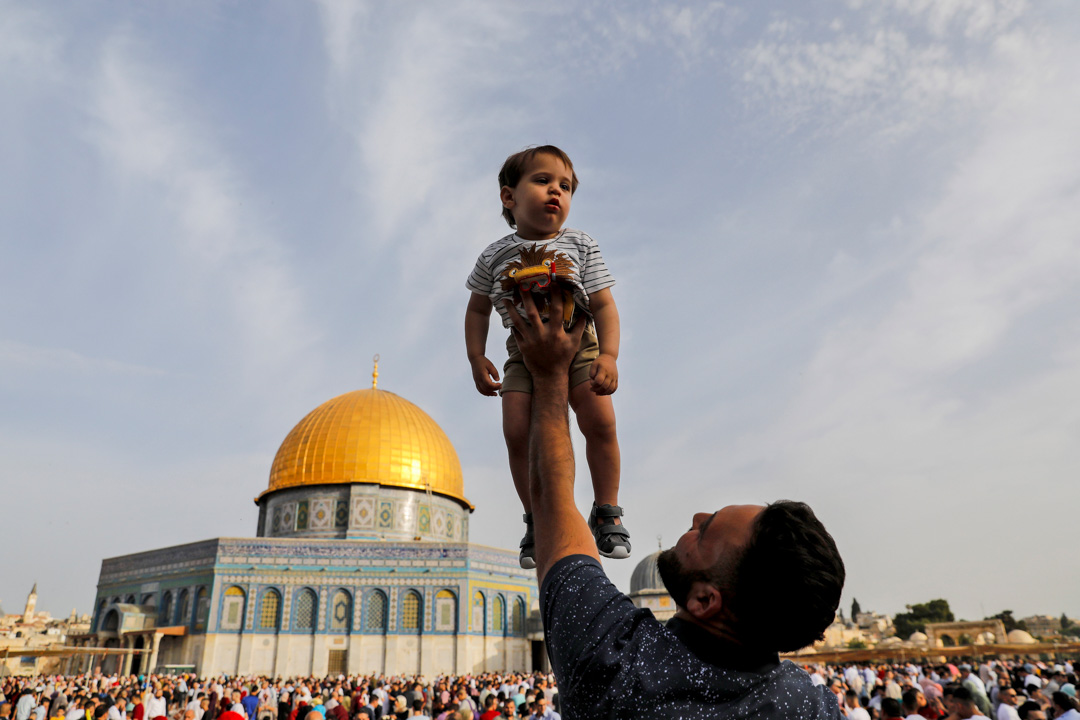 2019年6月5日,耶路撒冷老城阿克薩清真寺外,穆斯林們正做開齋節的清晨祈禱,一名父親托起了他的孩子。