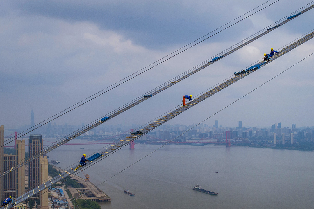 2018年5月8日,工人在中國湖北省武漢市橫穿長江的吊橋上工作。