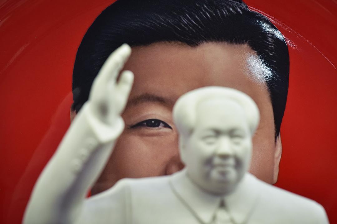 2018年2月27日,北京天安門廣場旁的一家紀念品商店,中國國家主席習近平的畫像,與共產黨領導人毛澤東的雕像。
