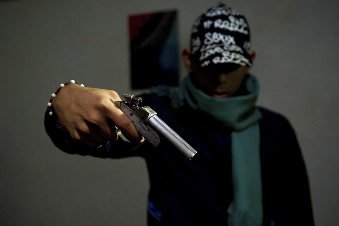 2013年6月27日,哥倫比亞卡利,一名黑幫成員手握自製槍支。