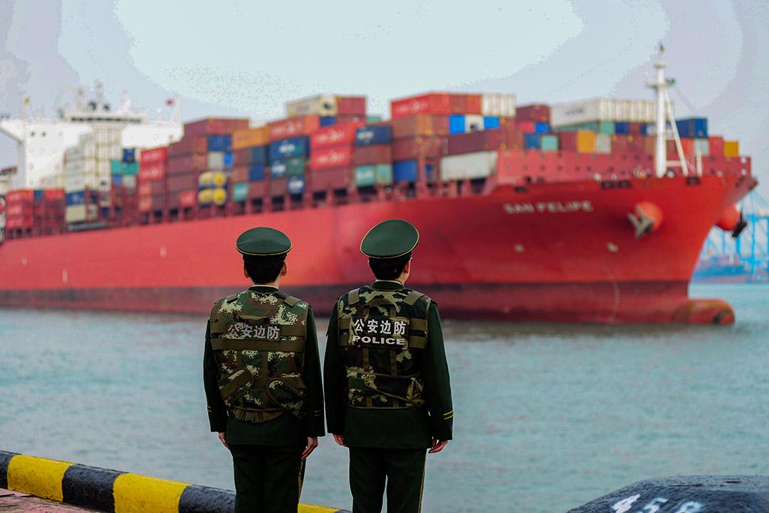 2018年3月8日,中國警察在中國山東省青島的一個港口觀看一艘貨船。