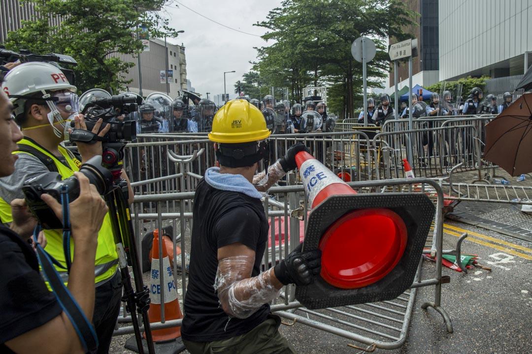 2019年6月12日,一名示威者與警察對峙時,拿起雪糕筒。