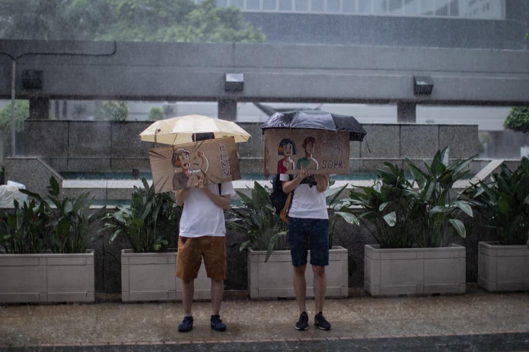大學生Alan、Jason在大雨下一手撐著雨傘一手舉著自製的「官逼民反」、「對唔住阻到你 SORRY」的紙牌,默默站在入境事務大樓外無聲抗議。 攝:Stanley Leung/端傳媒