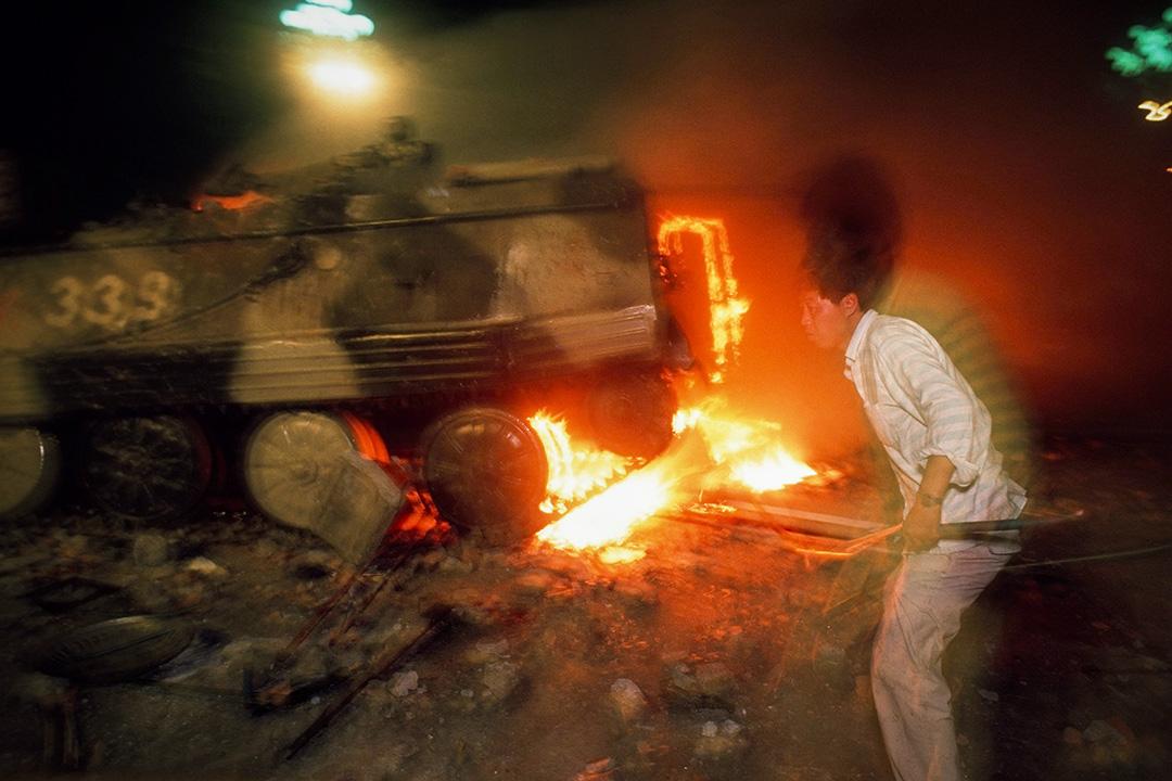 1989年6月4日,一名示威者與一輛燃燒的裝甲運兵車。 攝:Peter Charlesworth/LightRocket via Getty Images