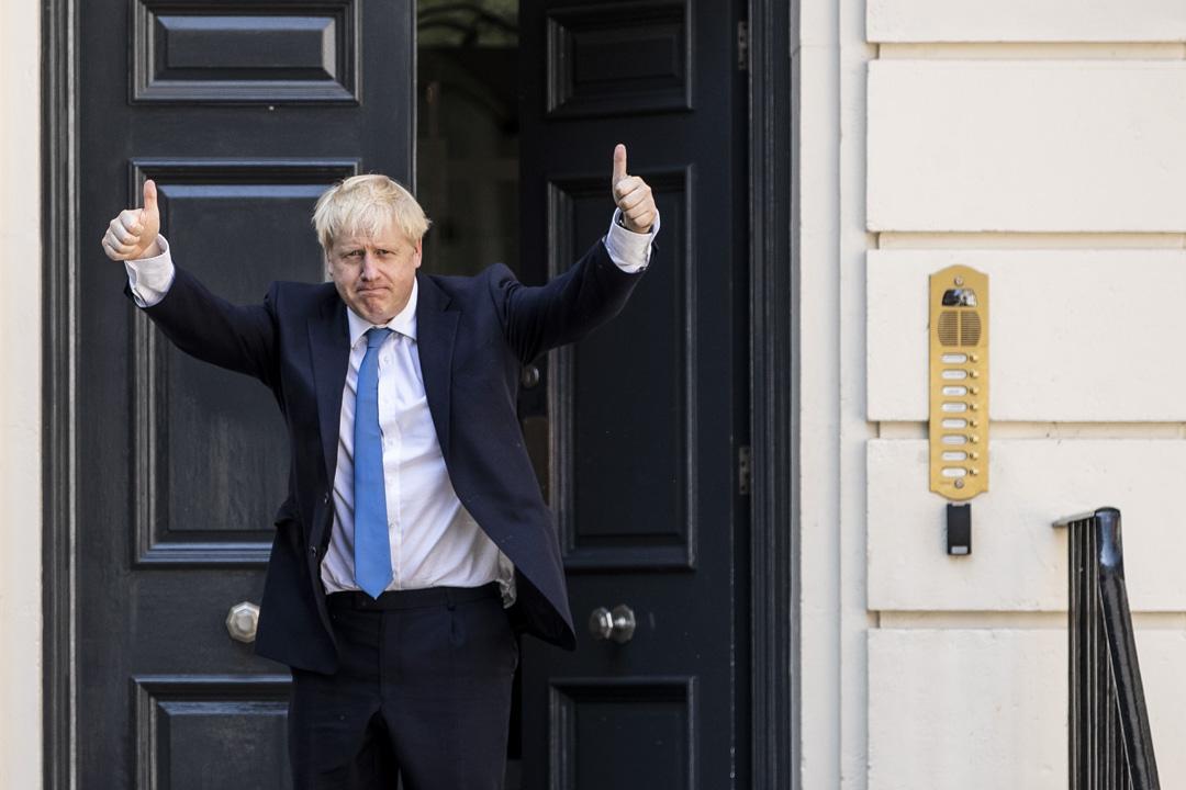 2019年7月23日,新當選的保守黨黨魁的約翰遜在英國倫敦的保守黨領導總部外舉起勝利手勢。 攝:Dan Kitwood/Getty Images