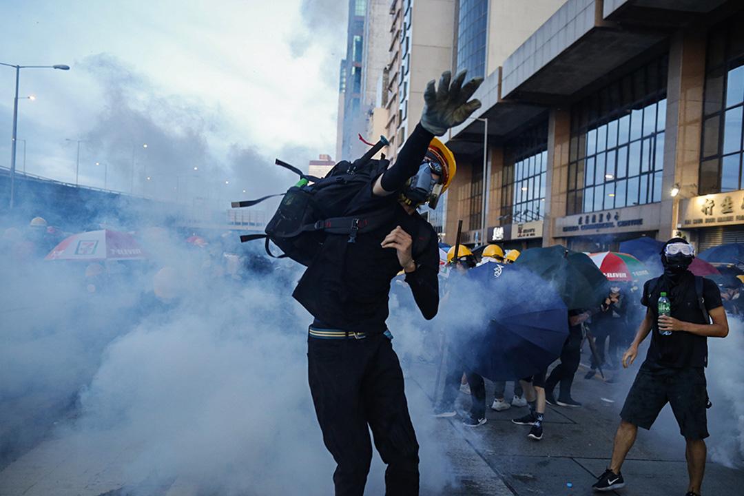 西環干諾道西,示威者向警察扔回剛向他們發射的催淚彈。