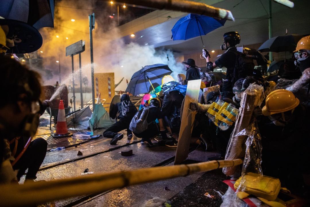 示威者以雨傘和消防喉作掩護,預備抵擋警察下一波的催淚彈。