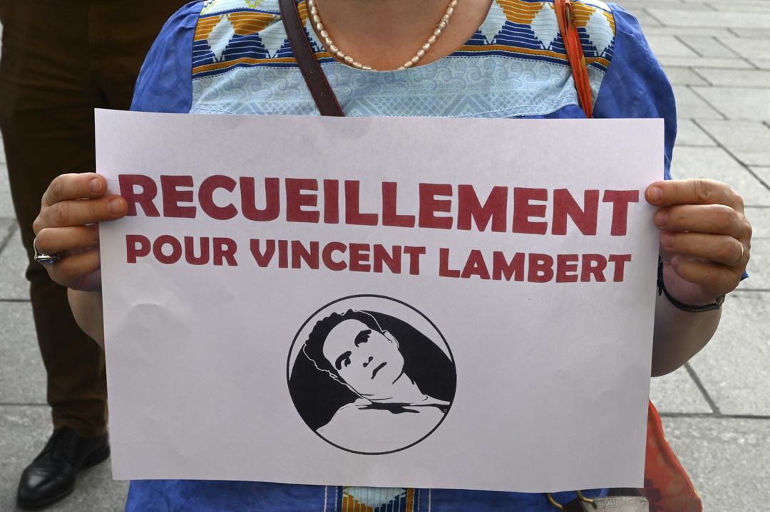 法國男子Vincent Lambert因車禍造成嚴重腦損且四肢癱瘓,是否安樂死讓他離開,多年來引發家屬之間的官司大戰。圖為2019年7月10日,在巴黎一個活動中,一名女士手持標語牌,上面寫著「Vincent Lambert的冥想」。 攝: Dominique Faget / AFP