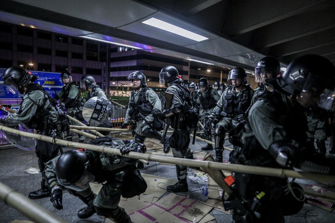 中環接駁IFC的行人天橋上,防暴警察拆去示威者設置的路障。