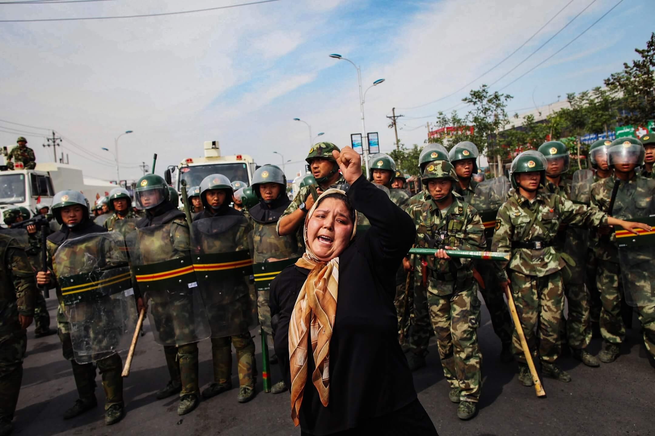 2009年7月7日,新疆維吾爾自治區首府烏魯木齊,一名維吾爾女子在警察防線前示威。 攝:Guang Niu/Getty Images