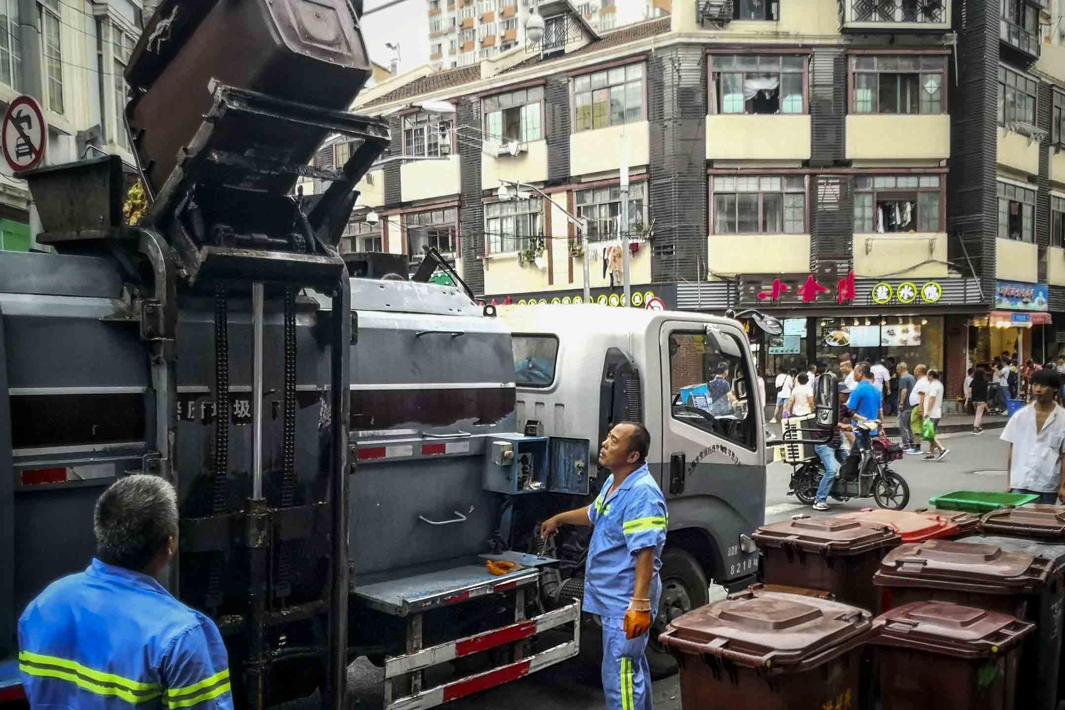2019年7月4日,上海穿著藍色工作服的人員在街上處理垃圾。 圖:IC photo