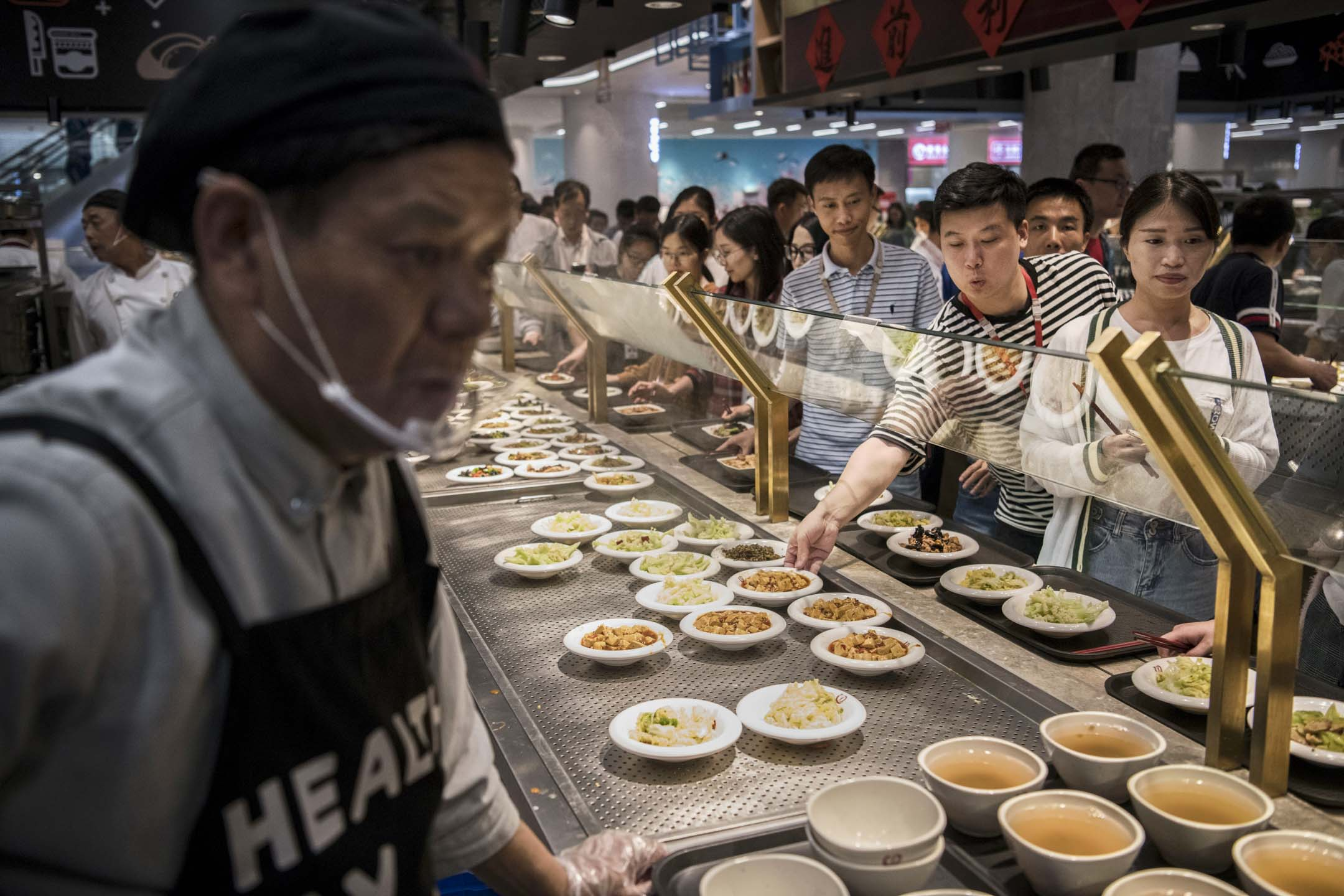 2019年4月12日,在中國深圳華為總部,員工在自助餐廳排隊等候午餐。 攝:Kevin Frayer/Getty Images