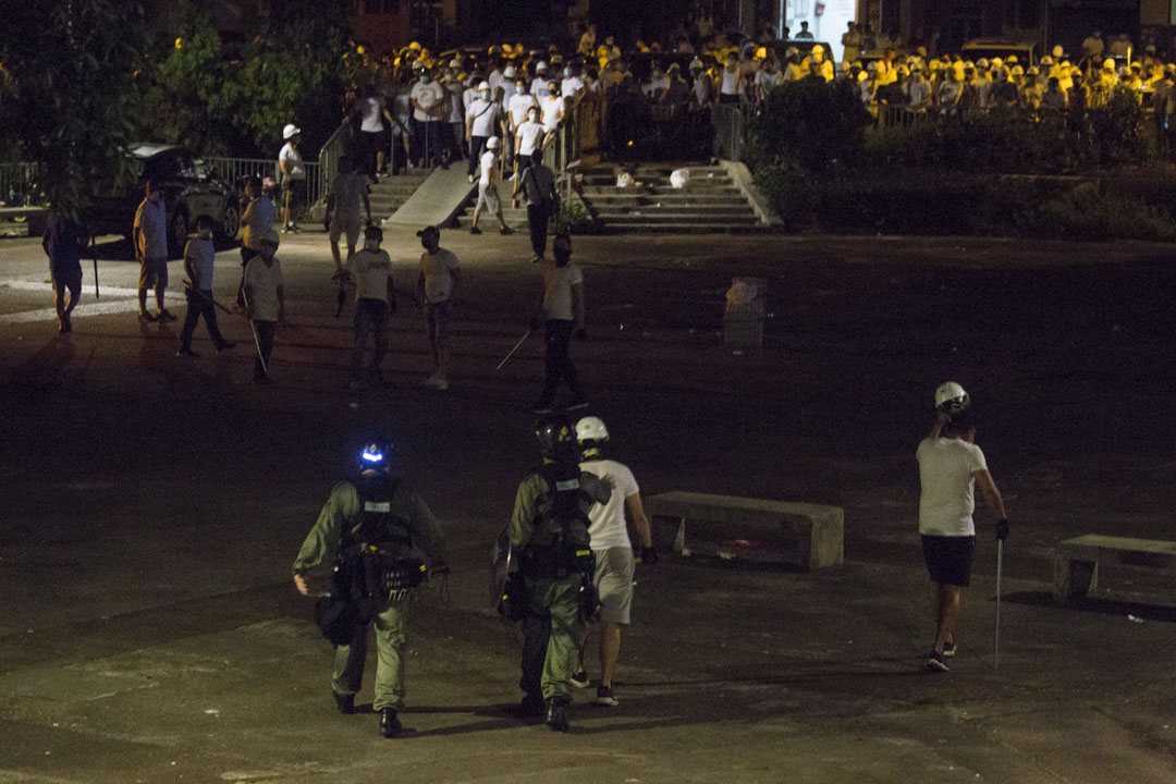 2019年7月22日,凌晨2時40 分,有市民在遠處呼喊挑釁南邊圍村集結的白衣人,數名白衣人手持棍棒突然衝上前,兩名防暴警察過去調停,期間拍打白衣人肩膀。 攝:林振東/端傳媒