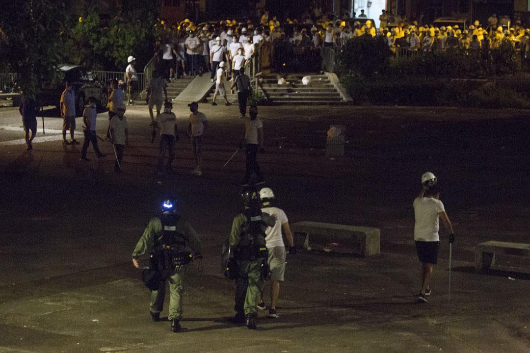 02:28,有市民在遠處呼喊挑釁南邊圍村集結的白衣人,數名白衣人手持棍棒突然衝上前,兩名防暴警察過去調停,期間拍打白衣人肩膀。