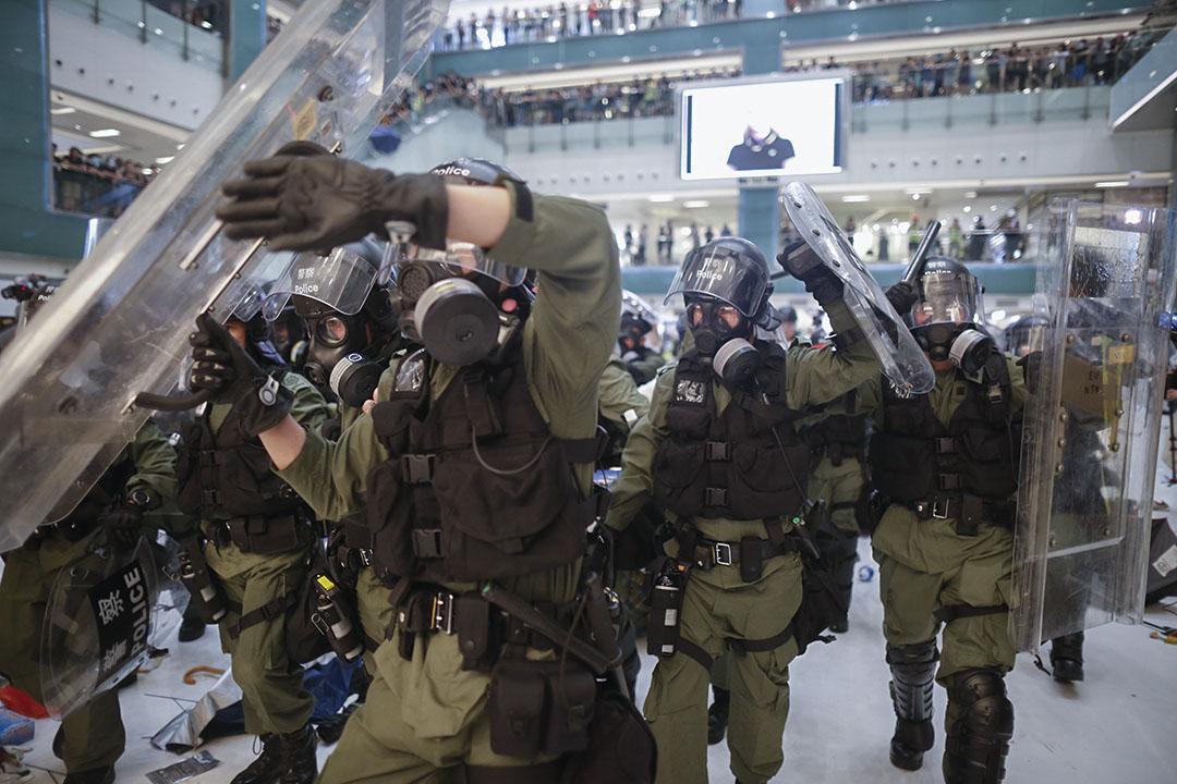 警察不斷推進和揮動警棍。