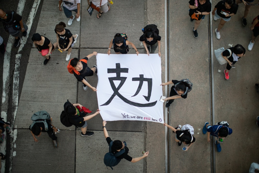 2019年7月1日,民陣發起七一大遊行,有參加者拿著寫有「攰」(累)字的橫幅。