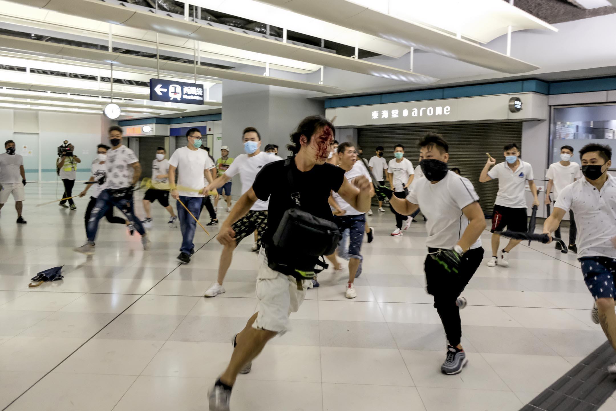 2019年7月22日,凌晨12時29分,大批白衣人撬開鐵閘衝進元朗港鐵站,以棍棒等物件追打市民。 圖:端傳媒