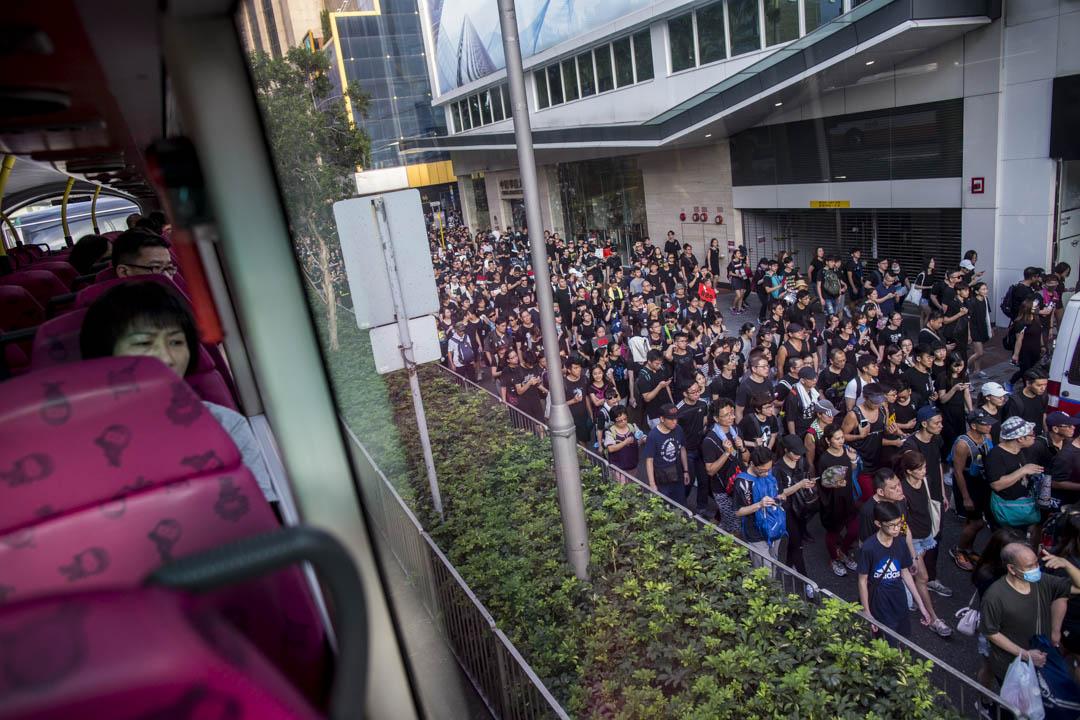 2019年6月16日,民陣發起反對《逃犯條例》修訂的「反送中」大遊行,共200萬人參與,其中遊行蔓延至告士打道行人路,乘客在巴士上觀看。 攝:林振東/端傳媒