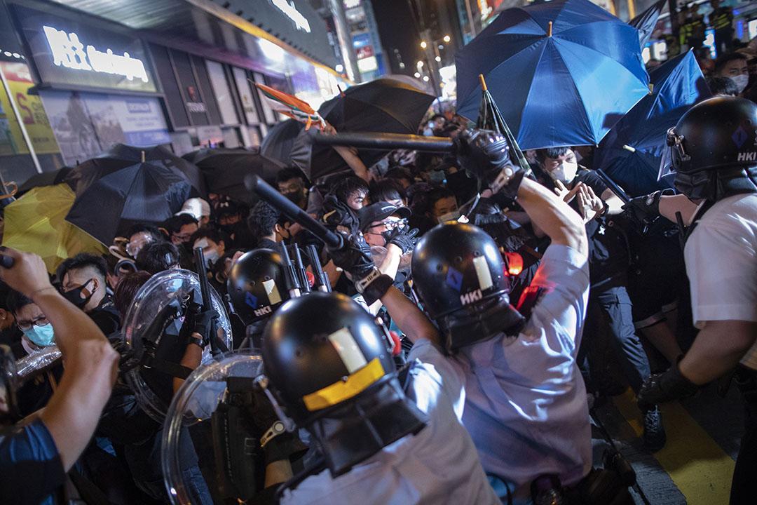 2019年7月7日晚上,警方在旺角彌敦道清場,並向示威者揮警棍。 攝:陳焯煇/端傳媒