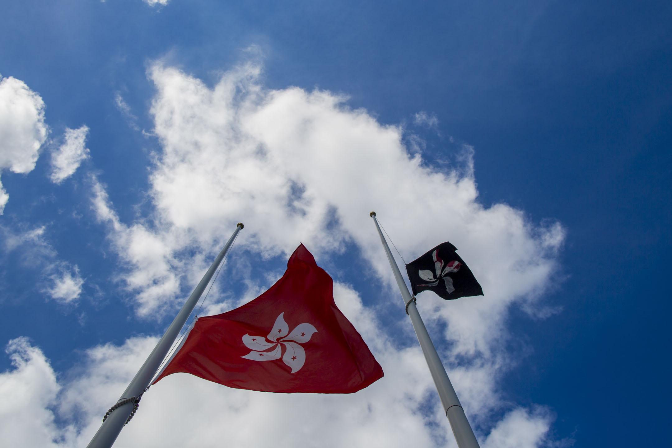 2019年7月1日,立法會廣場外旗杆上懸掛的國旗被人換上黑旗,特區區旗則被下半旗。 攝:林振東/端傳媒