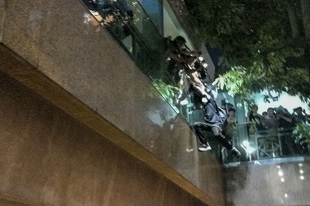 一名年輕人半身懸在空中,旁邊的兩名防暴警察和一名電視台攝影師合力將年輕人拉上來。