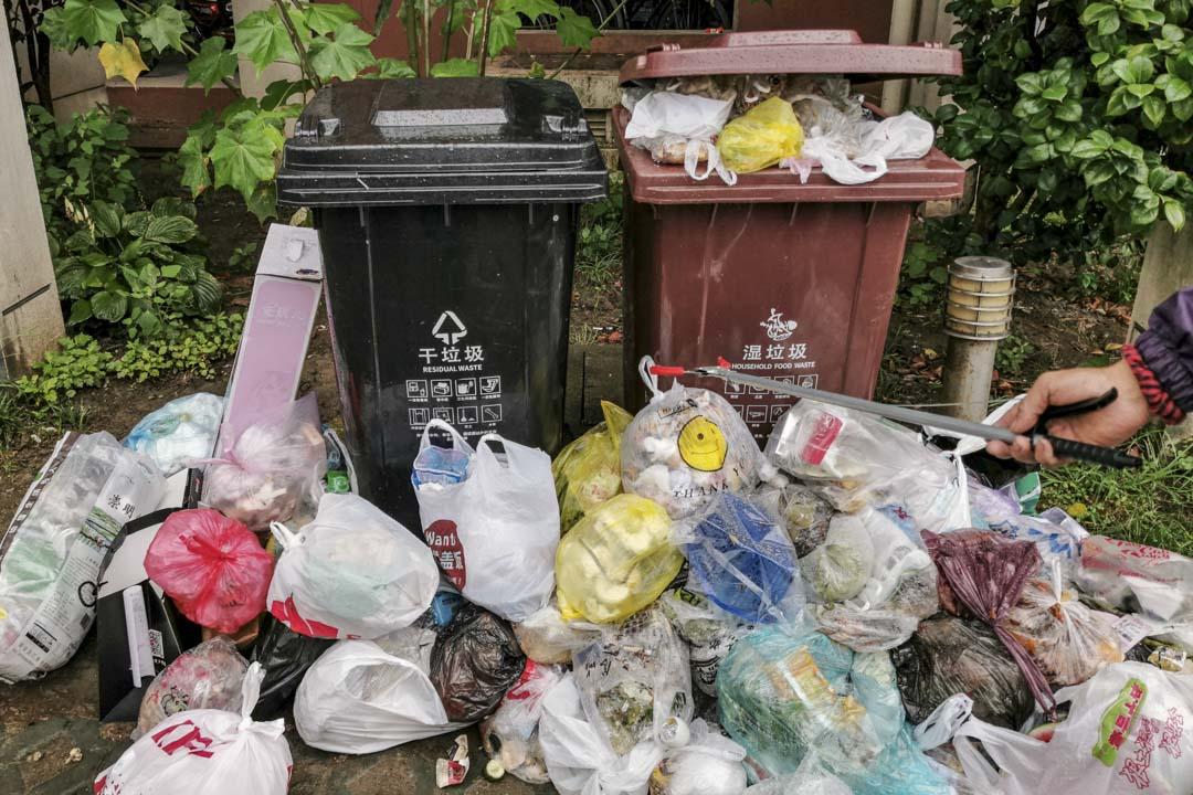 2019年7月10日,上海小區的分類垃圾桶外堆滿了袋裝垃圾,這些垃圾中多數是來不及清運的濕垃圾。
