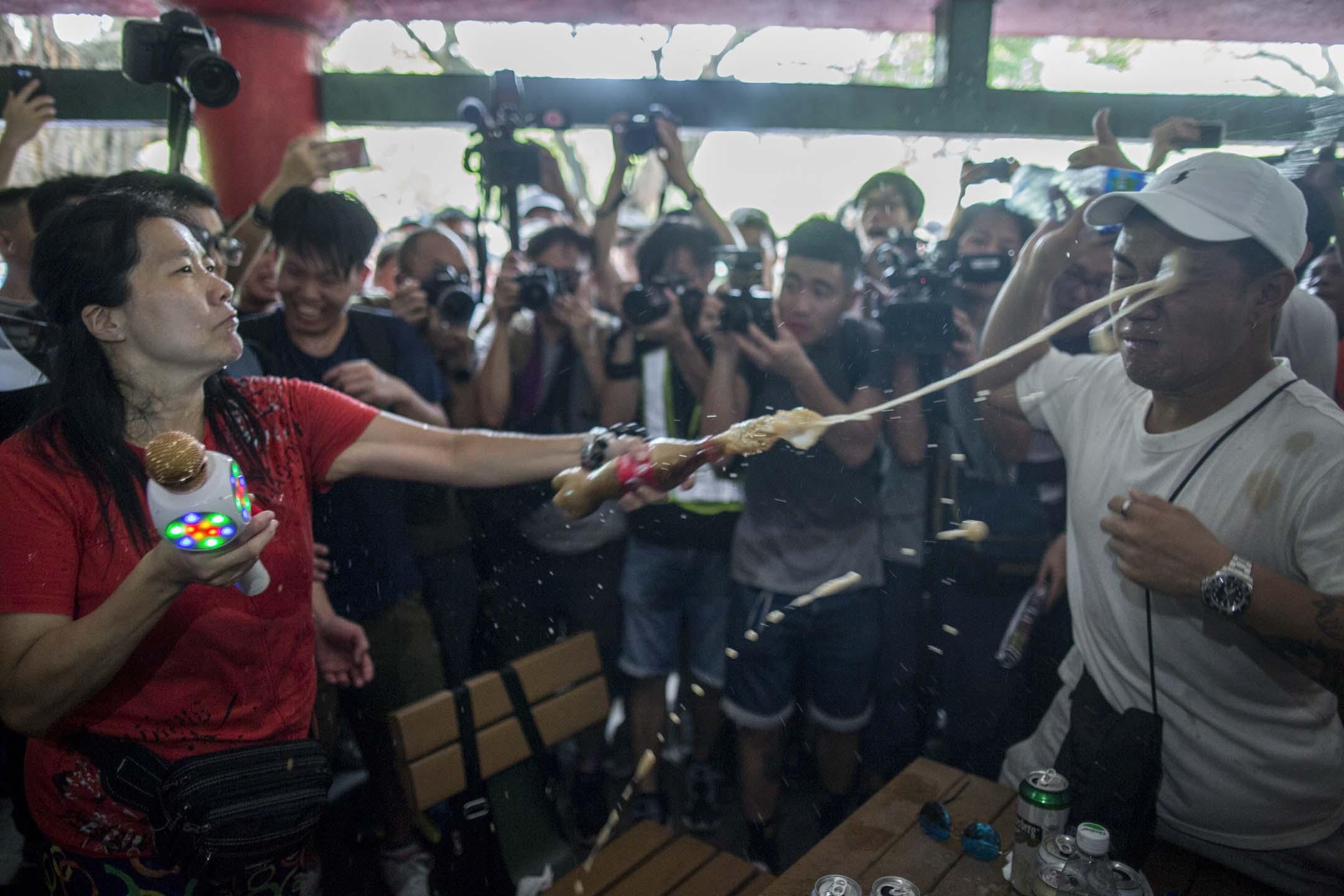 2019年7月6日,「光復屯門公園」行動,一名疑似歌舞團的表演者遭示威者圍罵,期間雙方互相向對方潑液體。 攝:林振東/端傳媒