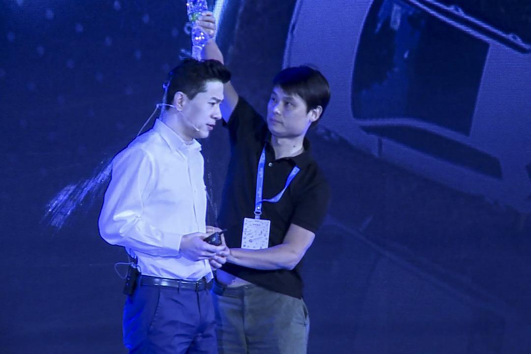 百度董事長李彥宏在AI開發者大會上演講時,一位身分不明的男子衝上演講台,朝他潑了一瓶水。 攝:Qian Ye/AFP/Getty Images