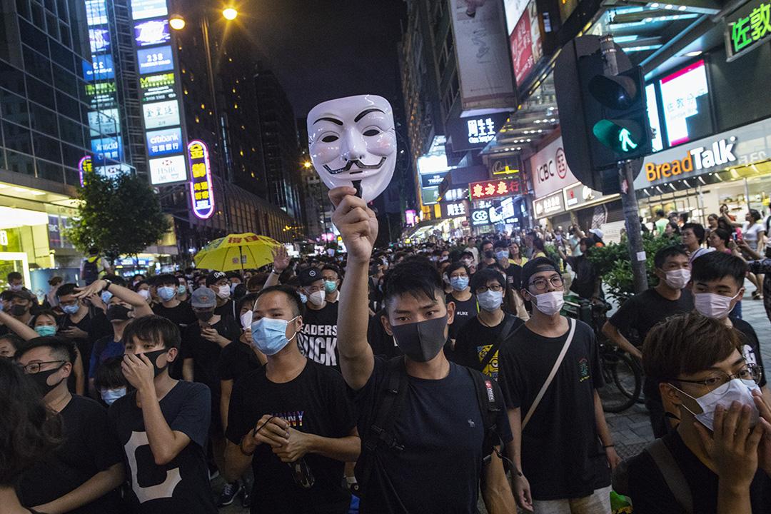 2019年7月7日,香港九龍區反修例大遊行,有人舉起象徵反極權政府的《V煞》面具。 攝:陳焯煇/端傳媒
