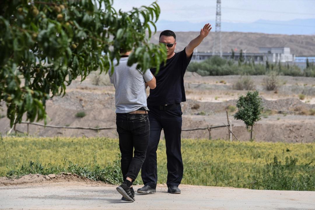 2019年6月2日,有外國媒體記者嘗試遠距離拍攝採訪新疆「再教育營」被一名身穿黑衣男子阻撓。