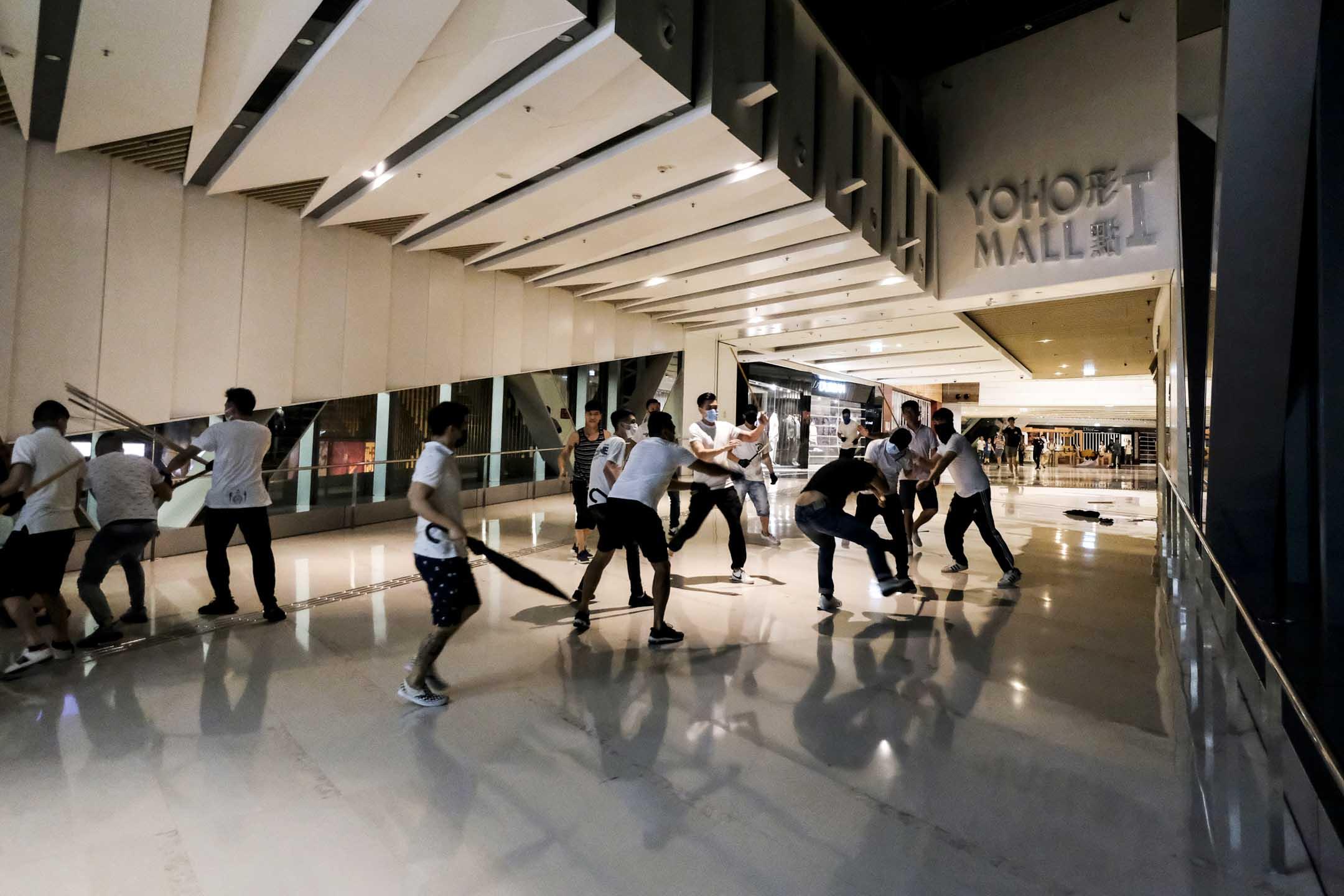 2019年7月22日,約凌晨12時29分,大批白衣人撬開鐵閘衝進元朗港鐵站,以棍棒等物件打市民,並追打至商場。 圖:端傳媒