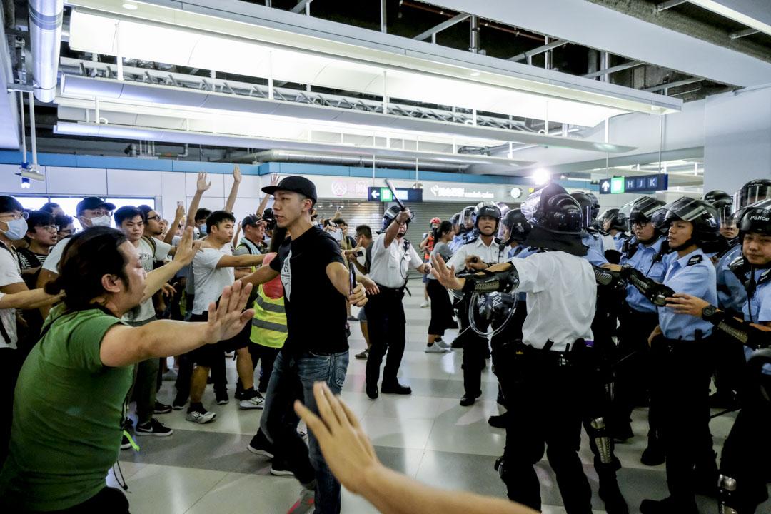 2019年7月21日,白衣人在西鐵元朗站大堂襲擊市民,其後警方抵達元朗站增援,其時白衣人已離開。市民鼓噪,警員一度揮動警棍,約半小時後全部警員離開西鐵元朗站。 圖:端傳媒