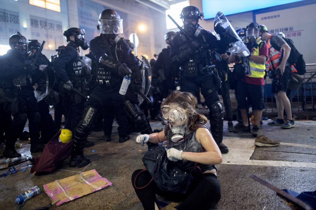 上環德輔道中,警察速龍小隊突擊示威者防線後,有示威者面部中了胡椒噴霧,坐在地上清理。