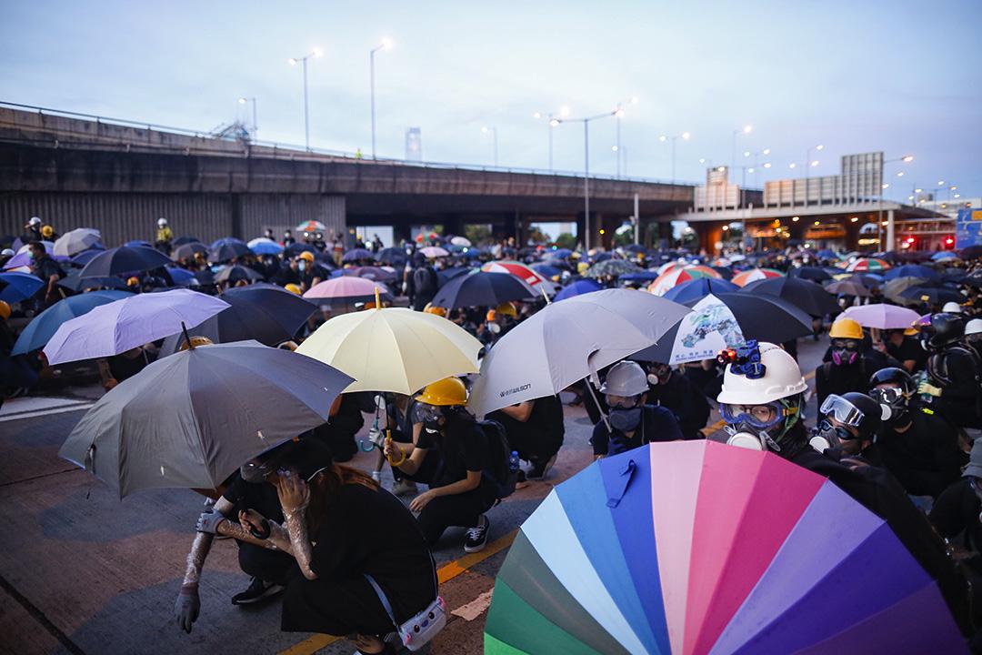 西環干諾道西,示威者蹲下撐著傘,堤防警察向他們發射不同類型的拋射物。
