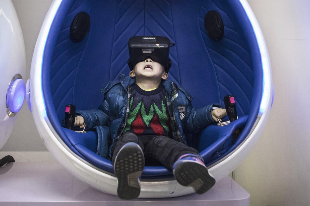 2016年11月26日,一名中國男孩在體驗一個過山車VR裝置。 攝:Kevin Frayer/Getty Image