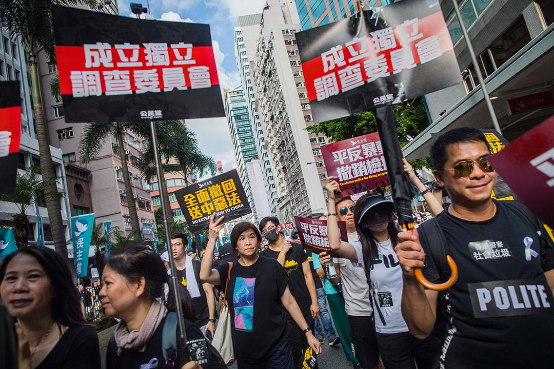 """2019年7月21日,市民參加遊行期間舉起""""成立獨立調查委員會""""的標語。"""