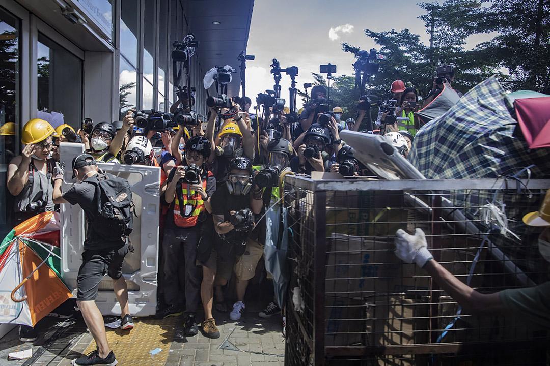 2019年7月1日,示威者在立法會外衝擊立法會的玻璃,記者在旁拍照。