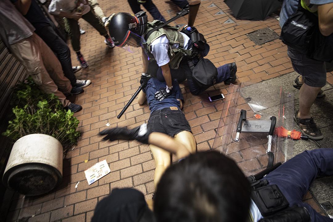 2019年7月7日晚上,警方在旺角彌敦道清場,警員制伏一名女示威者。 攝:陳焯煇/端傳媒