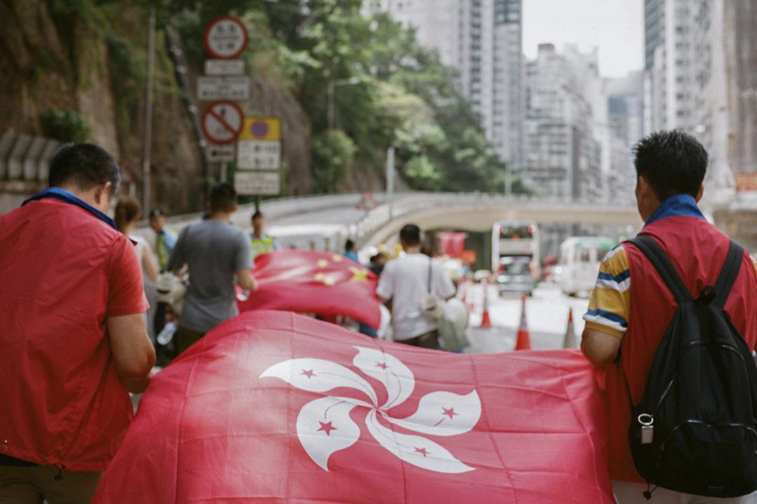 一個有遊行期間有參與者拉起香港區旗及中國國旗。 攝:Stanley Leung/端傳媒
