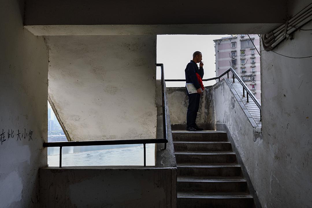 2019年4月23日,重慶渝中區的白象居小區,緊鄰重慶長江索道。圖為一名在樓梯間吸煙的男子。 圖:Imagine China