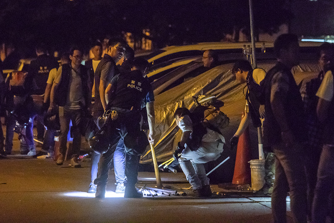 2019年7月22日,凌晨3時30分,警方在村內調查,檢示地上的鐵棍。 攝:陳焯煇/端傳媒