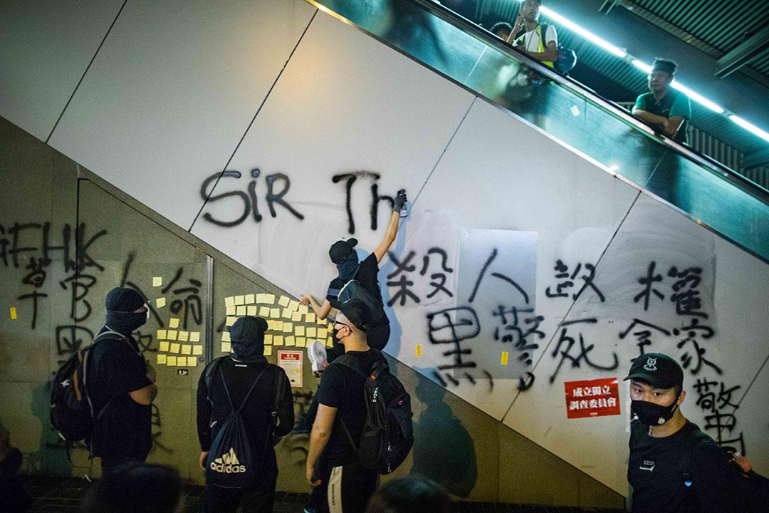 8月18日,夜晚11點金鐘,一名示威者在噴塗標語。