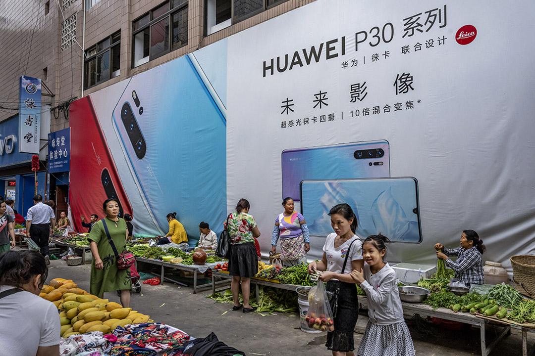 2019年6月1日,雲南省的一個市場,一名婦女與她的女兒在華為智能手機的廣告牌前走過。