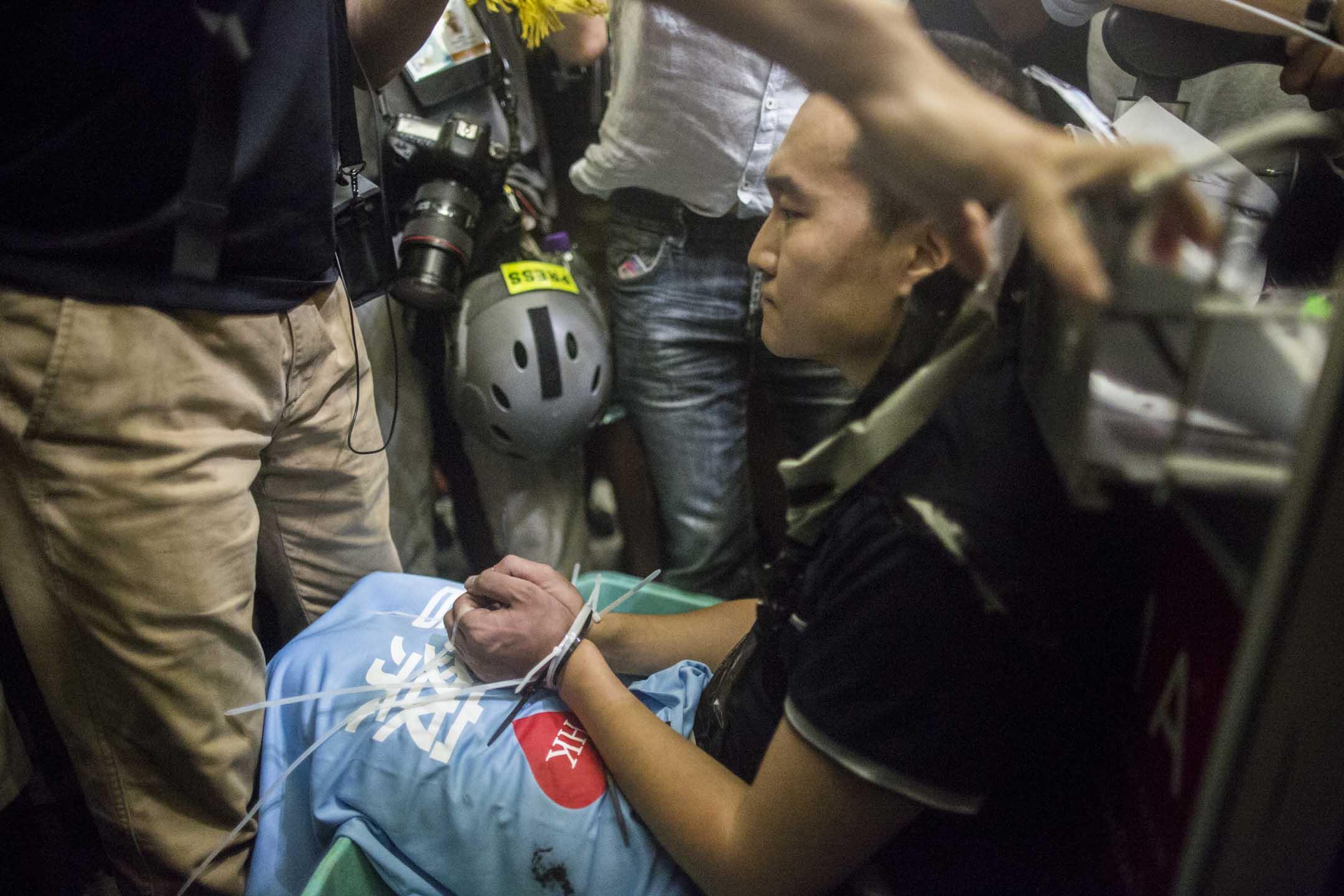 2019年8月13日晚上,一名自稱旅客的內地男子,其後被證實為《環球時報》記者付國豪,被示威者用膠索帶綁著手和腳,坐在行李車上。 攝:林振東/端傳媒
